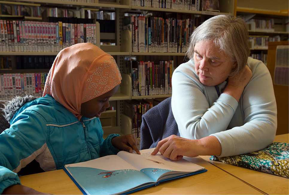 Young patron receiving homework help from a Library volunteer at our High Point branch