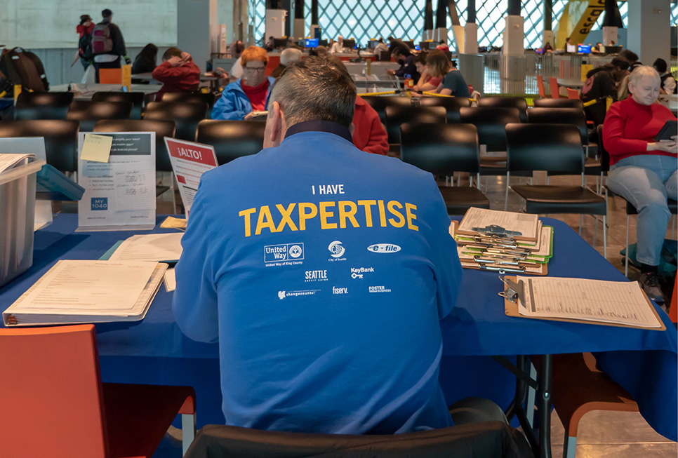 "Tax help volunteer wearing a t-shirt that says ""I have taxpertise."""