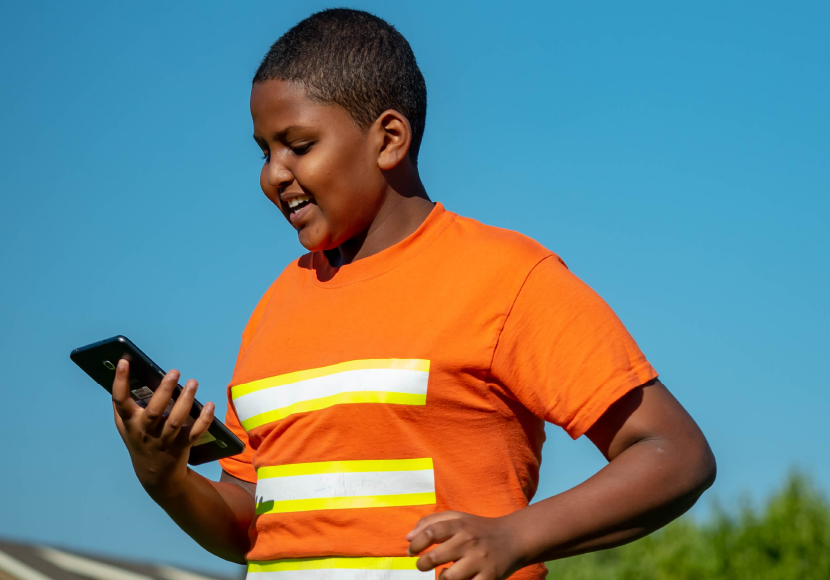 Young patron using a mobile device at a Summer of Learning event