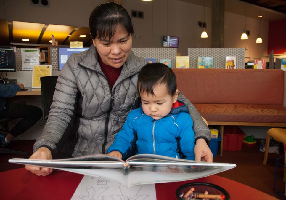 Family reading in the children's area at the International District/Chinatown Branch