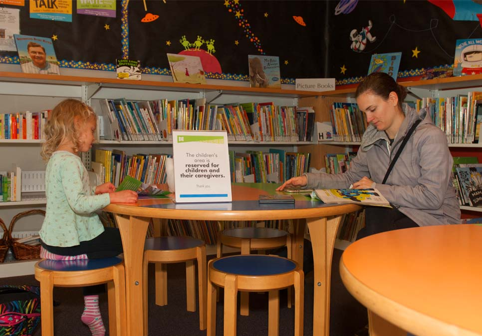 Family reading in children's area at the NewHolly Branch
