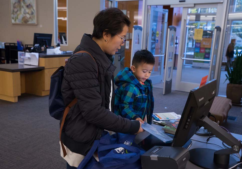 Family at self-checkout station at the Southwest Branch