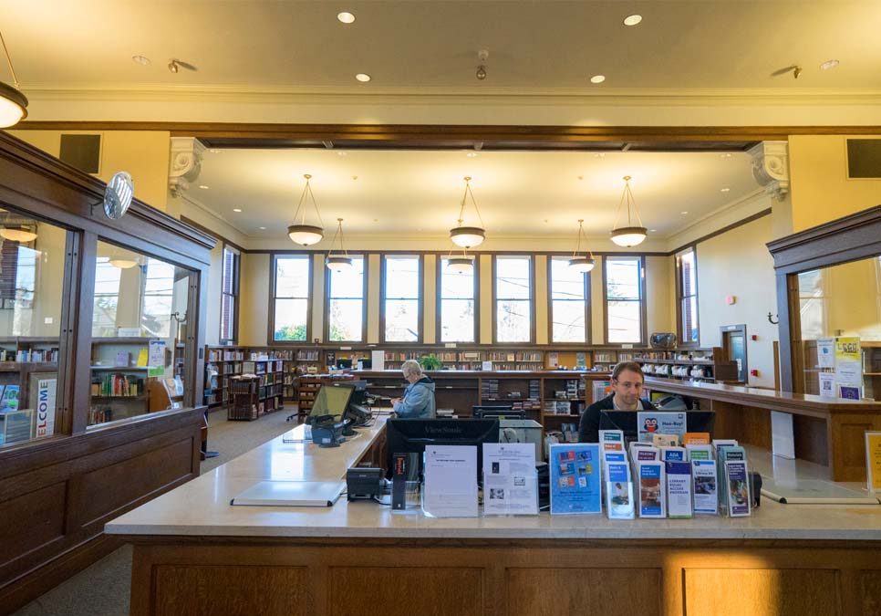 Library staff at service desk area at the West Seattle Branch