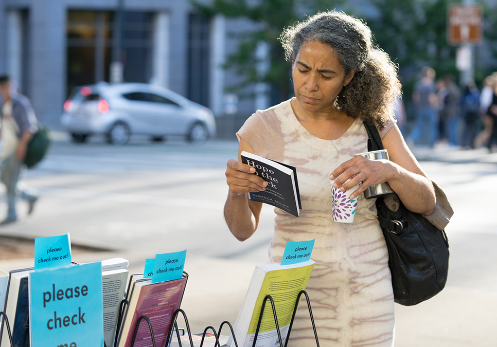 Patron looking at book at Art on the Plaza event at the Central Library in 2018