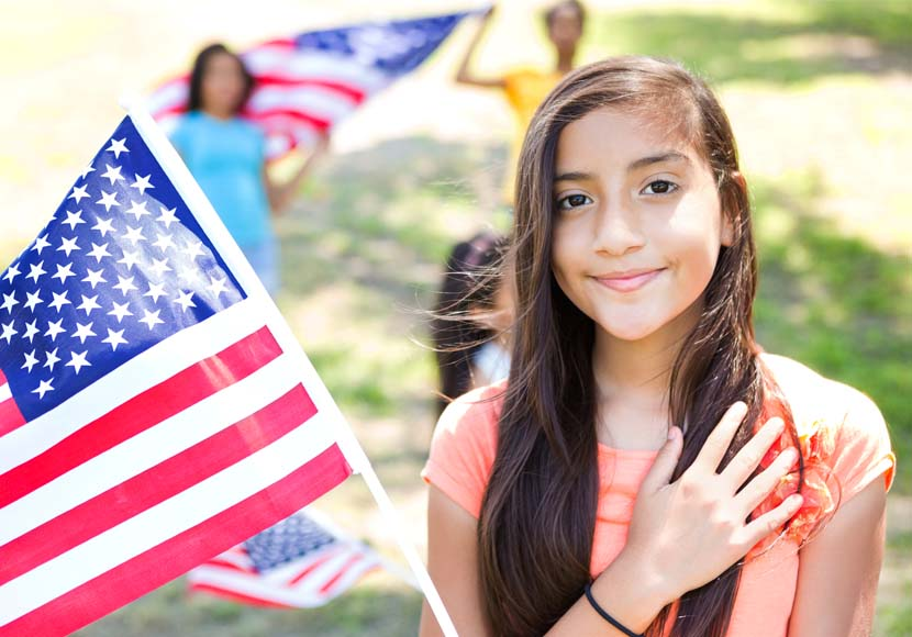 young girl next to american flag