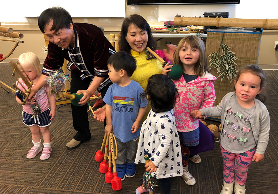 Kids from the Southwest Branch checking out musical instruments made of bamboo, with Canadian duo Khac Chi