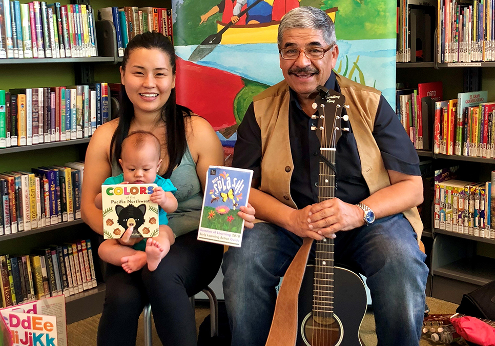 Mother and baby pose with their Summer of Learning prize book alongside singer Marco Cortes at the South Park Branch