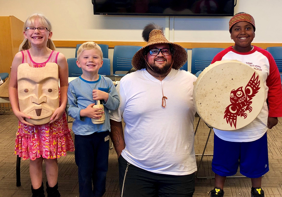 Indigenous storyteller and artist Ty Juvinel poses with kids after his Coast Salish Stories, Art and Design presentation at the Northeast Branch