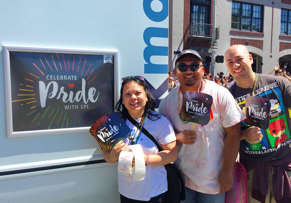 Library staff, friends and family posing with bookmobile at the Seattle Pride Parade
