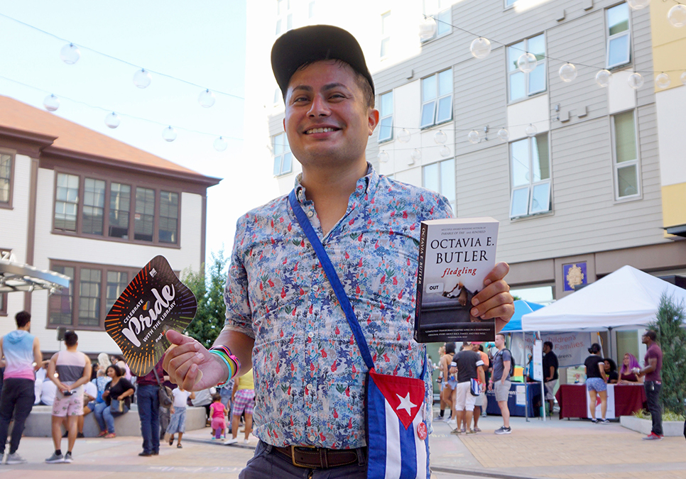 Attendee checking out book at Seattle Latinx Pride