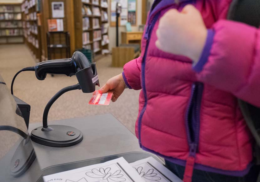 young patron checking out book with library card